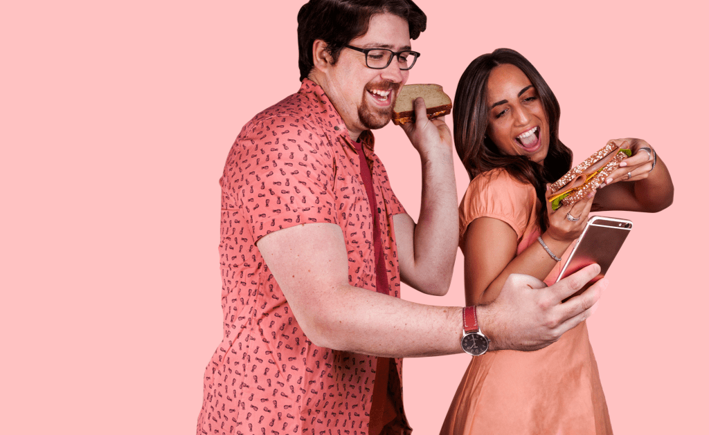 Man and woman taking a picture with sandwiches