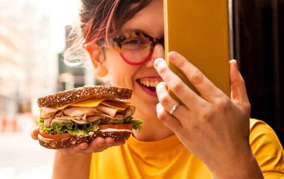 Woman taking a picture of a sandwich